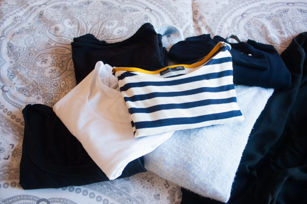 Assembly of black, white, striped, and light blue tops for packing
