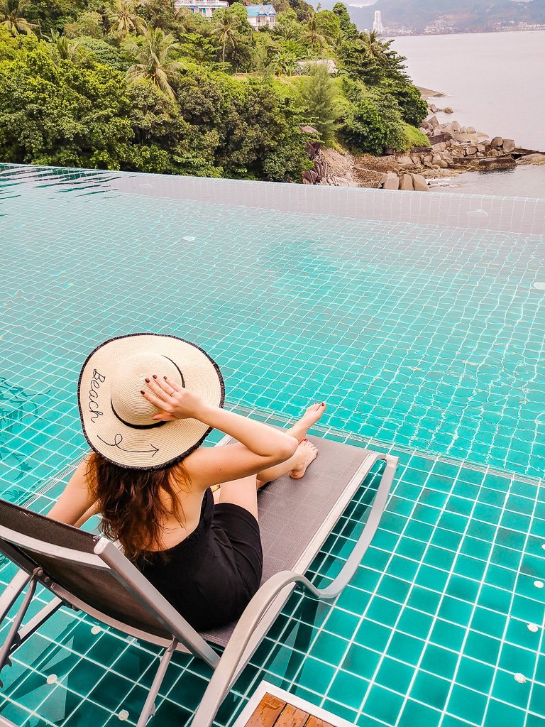 Bettina sitting at the infinity pool at U Zenmaya hotel in Phuket, wearing a beach hat