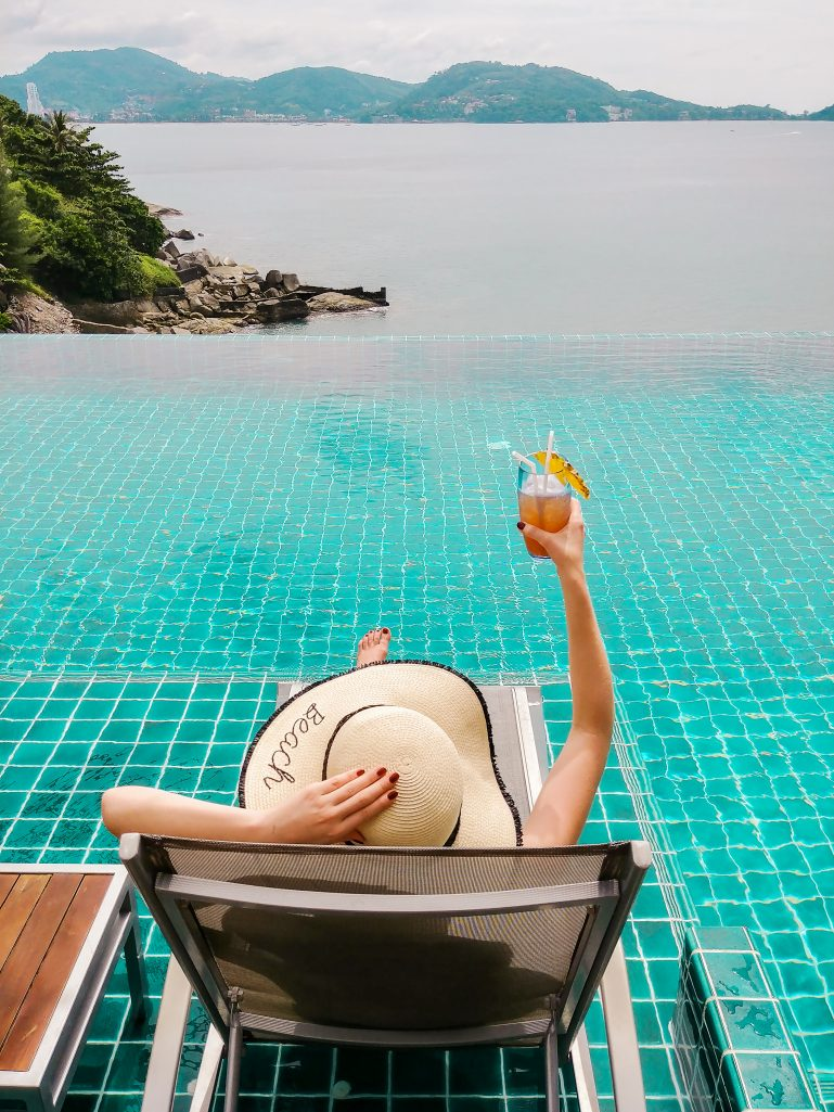 Bettina sitting at the infinity pool with view of the bay, holding a Pina Colada and holding her hat, U Zenmaya hotel, Phuket, Thailand