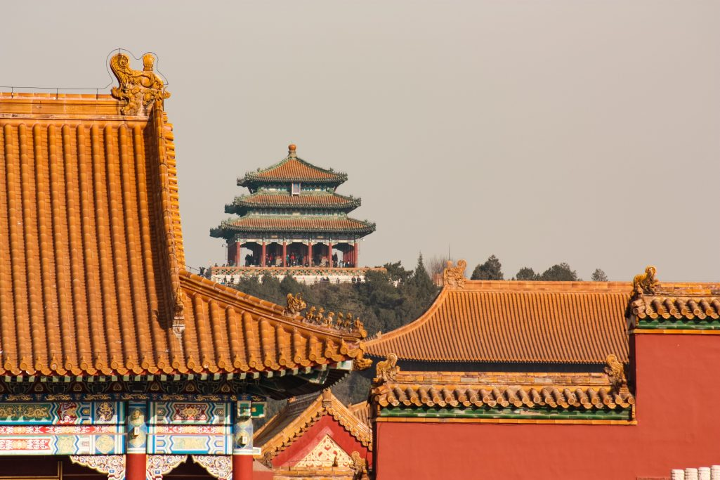 Palace and orange rooves in the distance showcasing the size of the forbidden city palace complex in Beijing