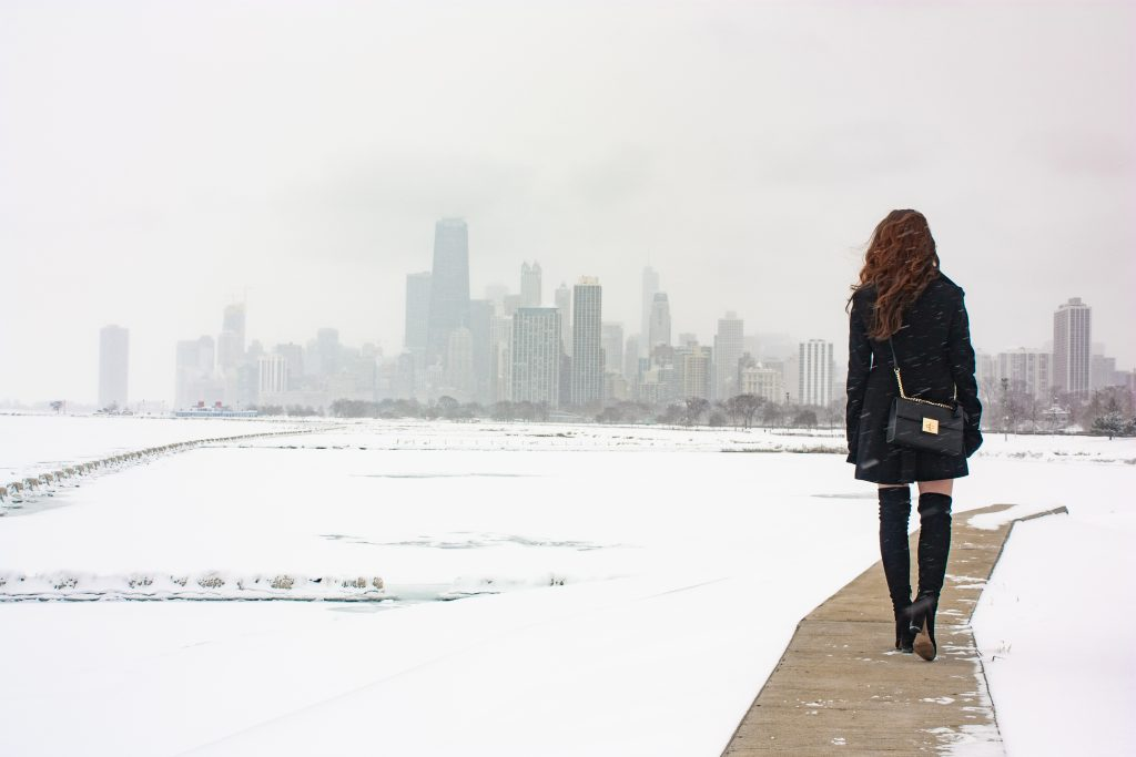 A walk along the snow covered lakeshore in Aldo over the knee boots, black a-line jacket, and cute Aldo purse with the Chicago skyline in the background.