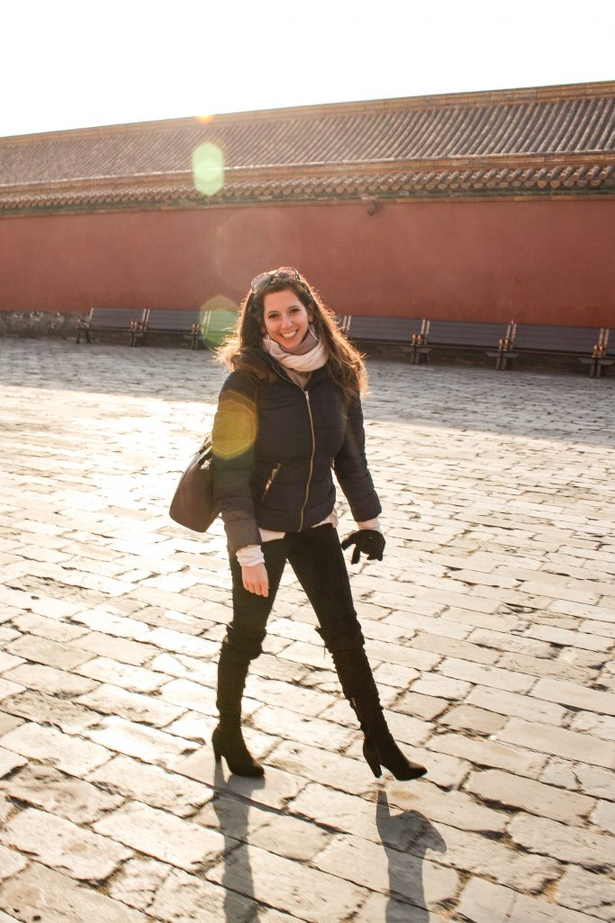 Bettina walking the cobble stones with sun reflection in the forbidden city, Beijing.
