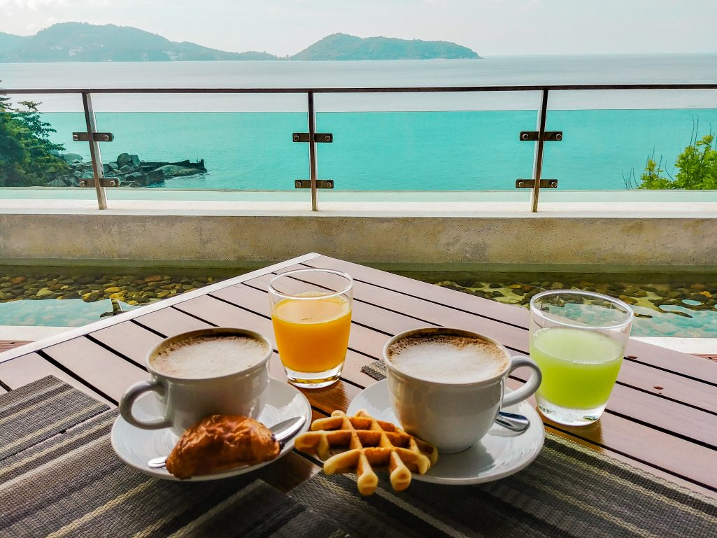 Coffee, juice, and pastries at U Zenmaya Hotel Phuket, overlooking a cloudy bay