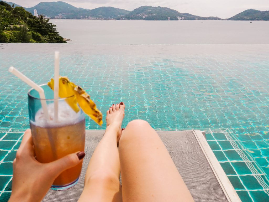 Bettina holding a Pina Colada at the infinity pool at U Zenmaya hotel in Phuket, Thailand